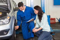 Mechanic showing customer the problem with car Royalty Free Stock Image