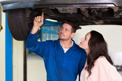 Mechanic showing customer the problem with car Stock Image