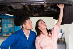Mechanic showing customer the problem with car Stock Images