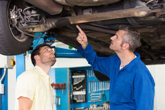 Mechanic showing customer the problem with car royalty free stock images
