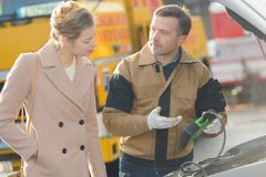 Mechanic showing diagnostic results to woman. Mechanic royalty free stock photography