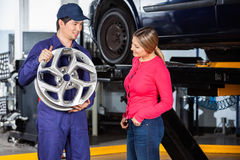 Mechanic Showing Hubcap To Customer Stock Image