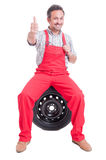 Mechanic showing like gesture sitting on wheel tire Stock Photos