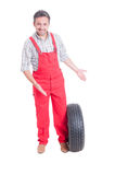 Mechanic showing new car tire Royalty Free Stock Image