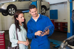Mechanic showing tablet pc to customer Stock Photos