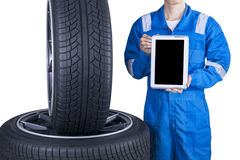 Mechanic showing tablet screen near tires Stock Photo