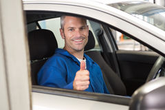 Mechanic showing thumbs up to camera. At the repair garage Stock Photos