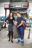 Mechanic Showing Tire to Customer. Full length portrait of female customer and mechanic holding tire in hand Stock Photo