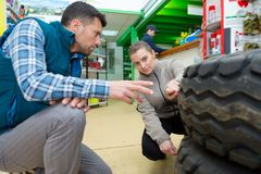 Mechanic showing tread tire to female colleague. Mechanic showing tread of tire to female colleague royalty free stock photography