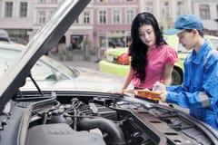 Mechanic shows the car problem on his client. Picture of a car mechanic explaining the car problems on his client with a clipboard at the road Stock Images