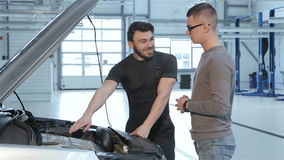 Mechanic shows problems of the car to the client. Bearded mechanic showing problems of the car to the client at service centre. Blond client in eyeglasse stock video footage