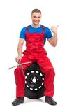 Mechanic sitting on tire and showing thumb up. Royalty Free Stock Image