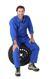 Mechanic sitting on a tyre Royalty Free Stock Photo