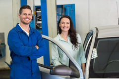 Mechanic smiling at the camera with customer. At the repair garage Royalty Free Stock Photo