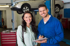 Mechanic smiling at the camera with customer. At the repair garage Stock Photo