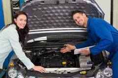 Mechanic smiling at the camera with customer. At the repair garage Stock Image