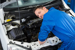 Mechanic smiling at the camera fixing engine Stock Images