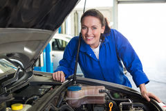 Mechanic smiling at the camera fixing engine Royalty Free Stock Image