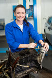 Mechanic smiling at the camera fixing engine Royalty Free Stock Images