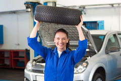 Mechanic smiling at the camera holding tire Royalty Free Stock Photography