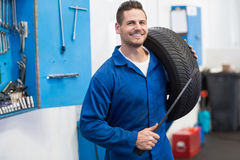 Mechanic smiling at the camera holding tire. At the repair garage Stock Photography