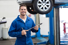 Mechanic smiling at the camera holding tool Royalty Free Stock Photo