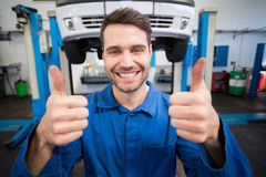 Mechanic smiling at the camera. At the repair garage Royalty Free Stock Photography
