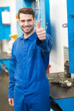 Mechanic smiling at the camera. At the repair garage Royalty Free Stock Images