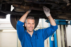 Mechanic smiling at the camera under car Stock Images