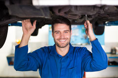 Mechanic smiling at the camera under car Stock Photo