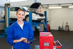 Mechanic smiling at the camera using tablet Stock Photography