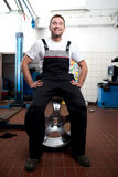 Mechanic smiling at work. Happy mechanic sitting on the wheel Royalty Free Stock Photo