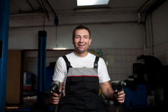 Mechanic smiling at work. Funny mechanic sitting on the wheel Royalty Free Stock Image