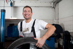 Mechanic smiling at work. Happy mechanic picking up the wheel Stock Image