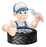 Mechanic with spanner and tire Royalty Free Stock Photography