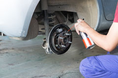 mechanic spray chemical to clean brake Stock Image