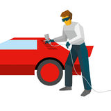 Mechanic spraying paint on red car from pulveriser Royalty Free Stock Images