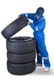 Mechanic and a stack of tires. Image of a car mechanic wearing uniform and puts a tire into a stack of tires, isolated on white background Royalty Free Stock Images