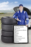 Mechanic with stack of tyres and signboard. Image of mechanic showing a road trip tips on the board and holding a wrench while standing close a pile of tires Royalty Free Stock Photo