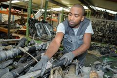 Mechanic at stack used car parts. Mechanic at stack of used car parts Stock Image
