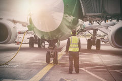 Mechanic standing by airplane at runway. Rear view of mechanic standing by airplane at runway royalty free stock images
