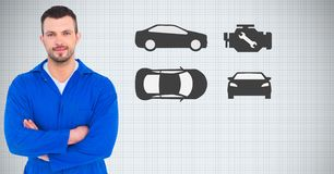 Mechanic standing with arms crossed against car icons in background Royalty Free Stock Image