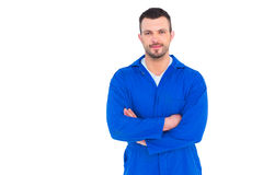 Mechanic standing arms crossed. Portrait of smiling male mechanic standing arms crossed on white background Stock Image
