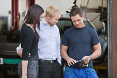 Mechanic standing with customers. Mature couple standing with mechanic outside the garage royalty free stock images