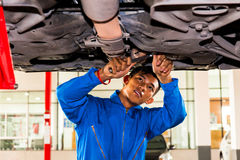 Mechanic standing and fixing under a lifted car with copy space.  Royalty Free Stock Photo