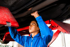 Mechanic standing and fixing under a lifted car with copy space Stock Photos