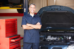 Mechanic standing in front of car Stock Images