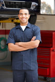 Mechanic standing in front of car. On ramp with arms crossed smiling at camera stock photo