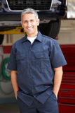 Mechanic standing in front of car. On ramp with hands in pockets smiling at camera royalty free stock image