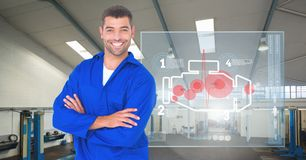 Mechanic standing with his arms crossed against car mechanics interface in background Royalty Free Stock Photo